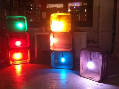 "These seven illuminated apple crates are lit with seven colored ceramic light-bulbs. The work is called ""Not Yet Title,"" by N.Y.U. student Michelle Lee."