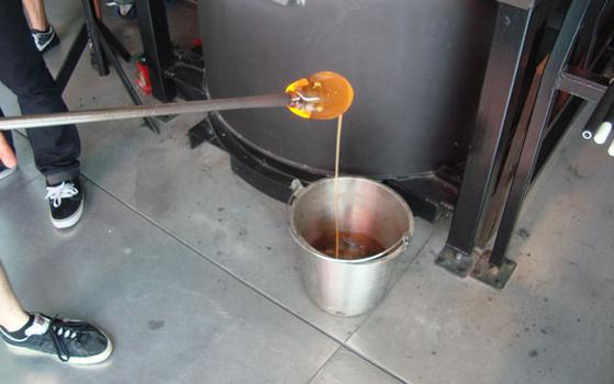 Excess molten glass is placed in a pail of water.