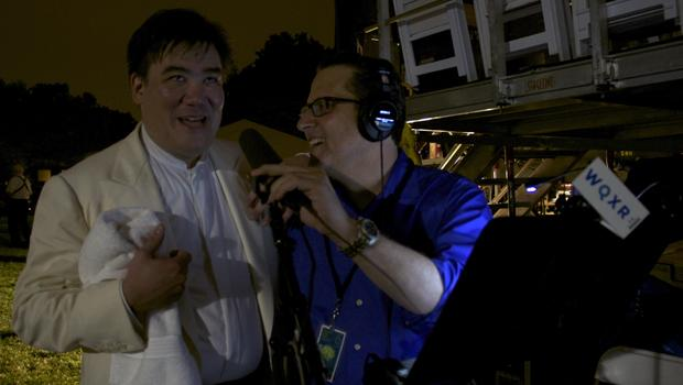 Alan Gilbert looks up at the fireworks following concert while talking with Elliott Forrest.