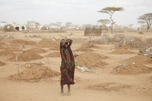 A young girl stands in front of 70 fresh graves for children who died of malnutrition, exhaustion, and other famine-related ills in Somalia.
