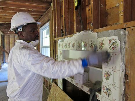 Jerome Wilson, 51, project site manager for the deconstruction project in Franklin, Michigan, shows off a tiled fireplace that is team will remove and be offered for purchase.