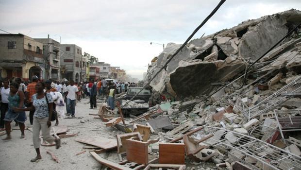 Haitians run past damaged buildings in Port-au-Prince