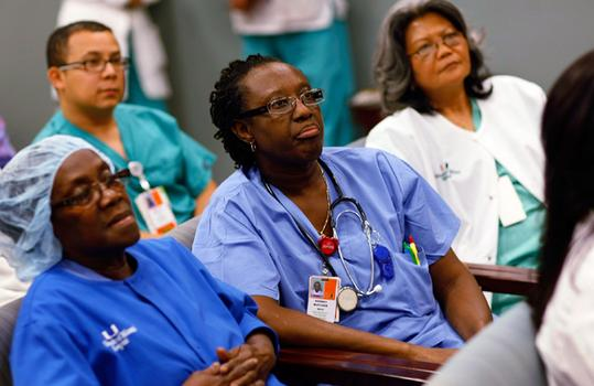 Registered nurses from Miami watch Obama\'s speech on TV.