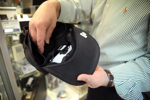 The hidden camera is revealed inside the baseball cap.