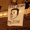 A St. Louis Symphony protester unfurls a banner at Powell Hall
