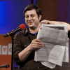 Eugene Mirman holds the full-page attack ad against Time Warner Cable he placed in The Greenpoint Gazette.