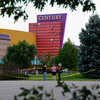 People stand in the parking lot outside the Century 16 movie theater where 12 people were killed in a shooting rampage on July 20 in Aurora, Colorado