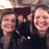 Radiolab producer Rachael Cusick standing and smiling with her grandmother, Marilyn Ryland, in a crowded room.