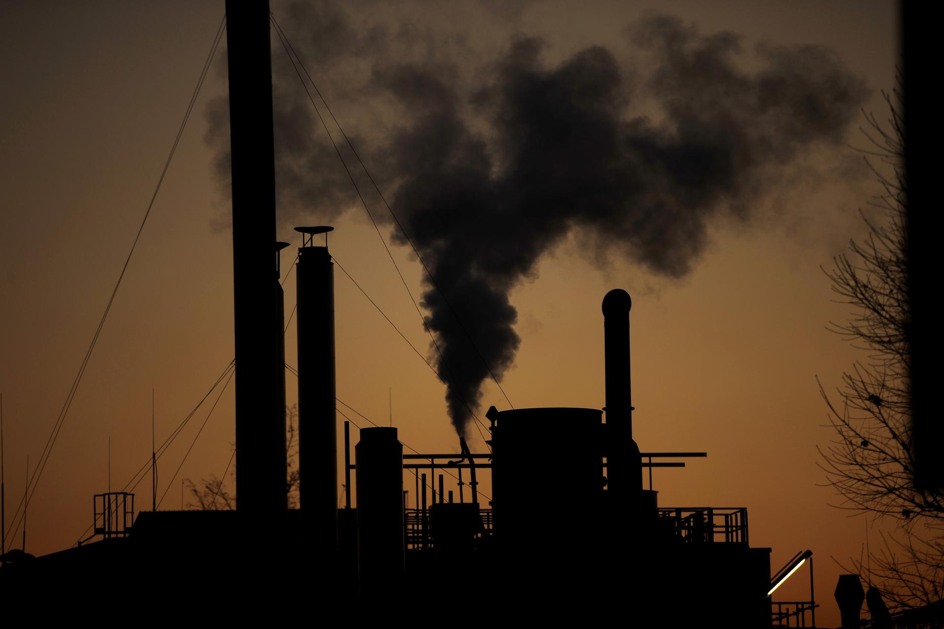 Silhouette of factory with smokestacks billowing smoke into a brownish-red sky