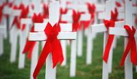 crosses in a graveyard with red AIDS ribbons