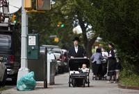 A Hasidic man pushes a stroller near the residence of Leibby Kletzky, a murdered eight-year-old boy who went missing from the Hasidic neighborhood of Borough Park, Brooklyn.