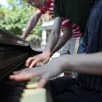 Three high school students playing a piano in Abe Lowenthal park in lower East Side in Manhattan waiting for a concert to begin on Make Music New York Day