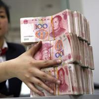 A Chinese bank worker arranges stacks of 100-yuan notes at a bank in Suining, southwest China's Sichuan province.