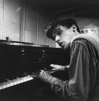 Brilliant Canadian pianist Glenn Gould as a young man, singing as he plays piano at a Steinway warehouse before choosing one for his recording session at Columbia Recording studios.