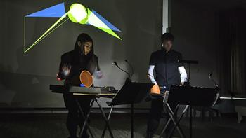 Two Mannes percussionists wear motion sensors in their arms to create a real-time projection on the rear screen.