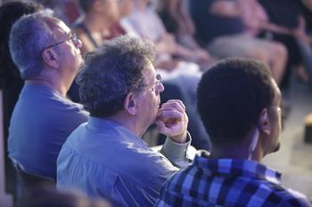 Philip Glass watches from the front row.