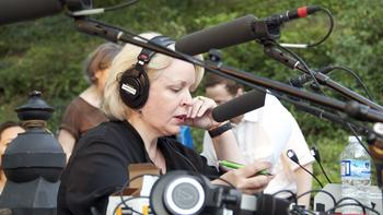 WQXR's Midge Woolsey hosts the live broadcast of the concert, amid the sounds of helicopters, birds and a nearby exercise class.