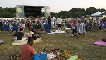 Despite the heat, concert-goers enjoy dinner in the park.