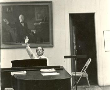 Fenno Heath (conductor, 1953-1992) in front of a picture of Marshall Bartholomew (conductor, 1921-1953), two of the seven men who have conducted the Yale Glee Club over its 150 years.