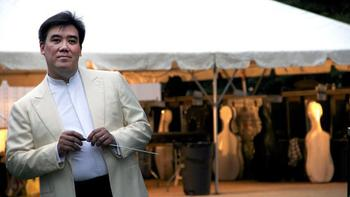 Alan Gilbert, with baton in hand, waits backstage before conducting the New York Philharmonic in Central Park on July 13, 2012.
