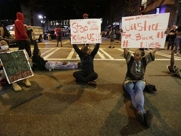 Demonstrators sit on a street during a protest of Tuesday's fatal police shooting of Keith Lamont Scott in Charlotte, N.C. on Wednesday, Sept. 21, 2016.