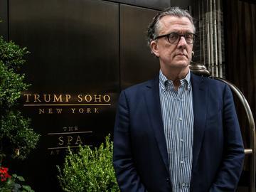 Kurt Andersen stands outside of Trump Soho