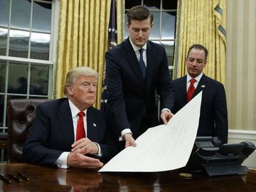 White House Chief of Staff Reince Priebus, right, watches as White House Staff Secretary Rob Porter, center, hands President Donald Trump a confirmation order for James Mattis as defense secretary, Fr
