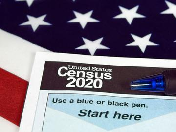 A piece of paper that reads 'United States Census 2020' with a blue pen and an American flag in the background