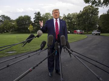 President Donald Trump stands in front of a tight cluster of microphones, raising one hand and speaking. The Washington Monument appears in the background.