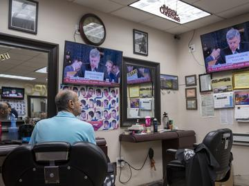 Barber Nat Yunayed watches impeachment hearings while waiting for customers in New York City on Wednesday, Nov. 13, 2019.