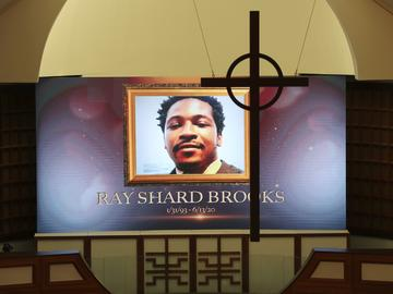 A cross hangs from the cathedral ceiling while Rayshard Brooks is memorialized on a screen during his public viewing at Ebenezer Baptist Church on Monday, Jun 22, 2020, in Atlanta.