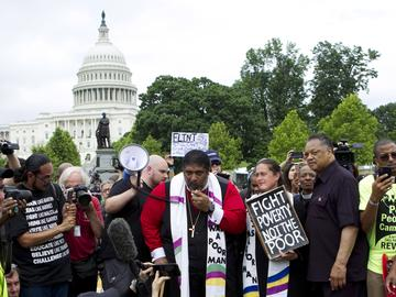 In this Saturday, June 23, 2018 file photo, Rev. Dr William Barber II accompanied by Rev. Dr. Liz Theoharis and Rev. Jesse Jackson speaks to the crowd outside of the U.S. Capitol.
