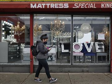 A woman wears a mask as she walks through downtown Newark.