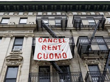 A sign hangs on an apartment building calling on New York Governor Andrew Cuomo to cancel the rent as part of an organized rent strike in conjunction with May Day in Brooklyn in 2020.