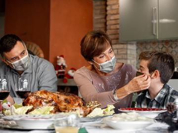 A family wears masks in front of a turkey at Thanksgiving.
