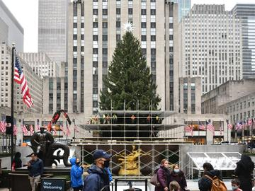 People walk in front of the Rockefeller Christmas tree where workers stand on scaffolding putting up lights.