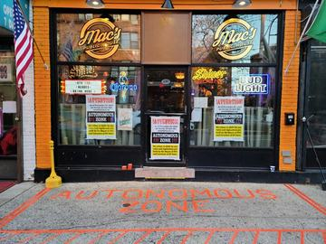 The exterior of Mac's Public House on Staten Island, which has put signs in the windows and a message painted on the sidewalk declaring the establishment an 'autonomous zone.'