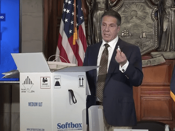 Gov. Andrew Cuomo holding a fake vial of the COVID-19 vaccine with a refrigerated box open near him