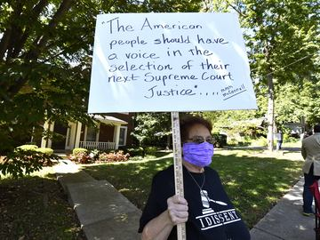 A protester stands outside the house of Senate Majority Leader Mitch McConnell, R-Ky., in Louisville, Ky., Saturday, Sept. 19, 2020. McConnell vowed on Friday night, hours after the death of Ginsburg.