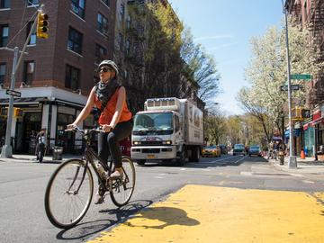 A woman crosses MacDougal street in lower Manhattan on her bicycle