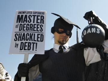 In this Oct. 6, 2011 photo, Gan Golan, of Los Angeles, dressed as the 'Master of Degrees,' holds a ball and chain representing his college loan debt, during Occupy DC activities in Washington.