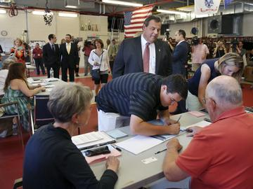 New Jersey Gov. Chris Christie, top, looks on as his son, recent Princeton graduate, Andrew Christie signs in to vote at Brookside Engine Company 1 firehouse in Mendham Township, N.J. on June 7, 2016.