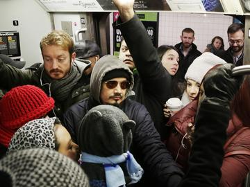 Commuter crowded on the L train as service is operating at near peak capacity.
