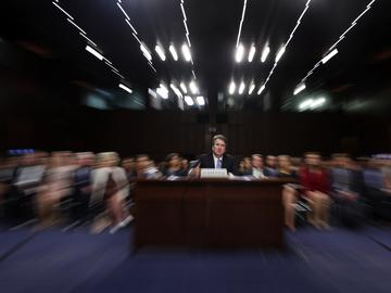 In this photo taken with a slow shutter speed and a zoom, President Donald Trump's Supreme Court nominee, Brett Kavanaugh testifies before the Senate Judiciary Committee on Capitol Hill