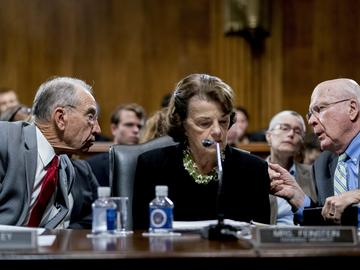 Senate Judiciary Committee Chairman Chuck Grassley, R-Iowa, left, accompanied by Sen. Dianne Feinstein, D-Calif., the ranking member, center, speaks with Sen. Patrick Leahy, D-Vt., right.