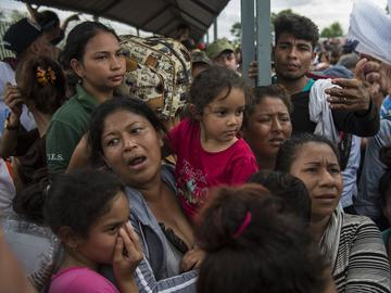 Migrants stand next to the gate between the Guatemalan and Mexico border, waiting to let in after being checked out by Mexican authorities in Ciudad Hidalgo, Mexico, Saturday, Oct. 20, 2018.