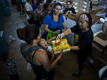 In this Sept. 7, 2018 photo, a woman with her child receives free diapers and shower gel, as she and others line up for food and other donated staples from the MARC