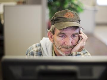 In this Oct. 20, 2014 photo, unemployed coal miner Eddie Jones looks for jobs on a computer at the Kentucky Career Center in Harlan, Ky.