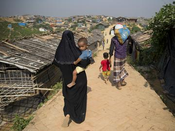 A Rohingya refugee family walks back with relief material collected from aid agencies inside Balukhali refugee camp near Cox's Bazar, in Bangladesh, Saturday, Nov. 17, 2018.