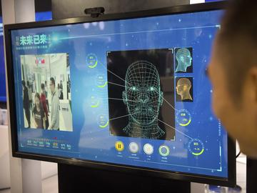A man watches as a visitor tries out a facial recognition display at a booth for Chinese tech firm Ping'an Technology at the Global Mobile Internet Conference (GMIC) in Beijing, Thursday, April 26.